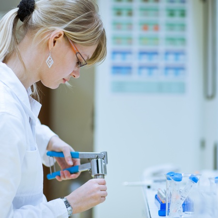 female researcher carrying out research experiments in a chemistry lab (color toned image) photo