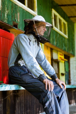 Beekeeper by an apiary observing carefully his bees photo