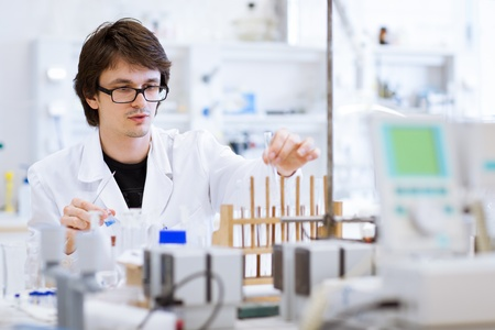 young, male researcherchemistry student carrying out scientific research in a lab (shallow DOF; color toned image)