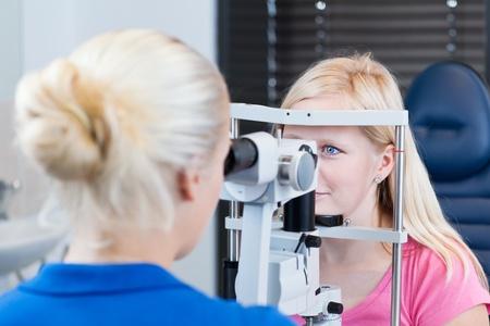 optometria: Koncepcja optometria - Å'adna, mÅ'oda kobieta pacjenta majÄ…cego oczy przebadane przez lekarza okulistÄ™ (kolor stonowanych obraz, pÅ'ytkie DOF) Zdjęcie Seryjne