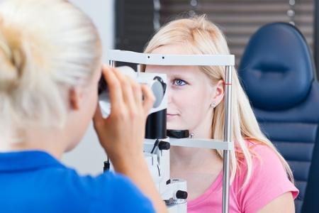 oculista: concepto de Optometría - guapa, joven paciente tener sus ojos examinados por un médico de ojo (color en tonos imagen; DOF superficial)