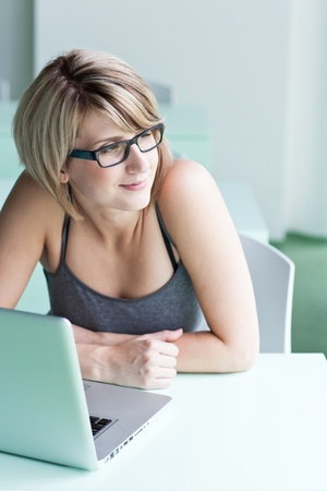 Portrait of a young woman pensively looking out of the window while sitting in front of her laptop Stock Photo - 10895427