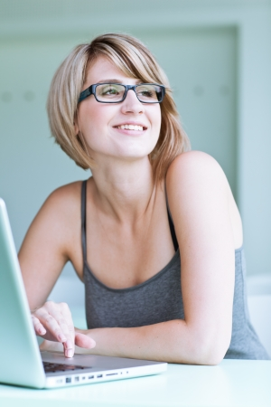 wearing glasses: Portrait of a young woman pensively looking out of the window while sitting in front of her laptop