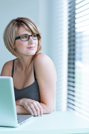 new thinking: Portrait of a young woman pensively looking out of the window while sitting in front of her laptop