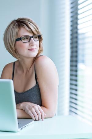 new thinking: Ritratto di una giovane donna pensosa guardando fuori dalla finestra, seduti di fronte al suo computer portatile