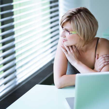 Portrait of a young woman pensively looking out of the window while sitting in front of her laptop Stock Photo - 10895221
