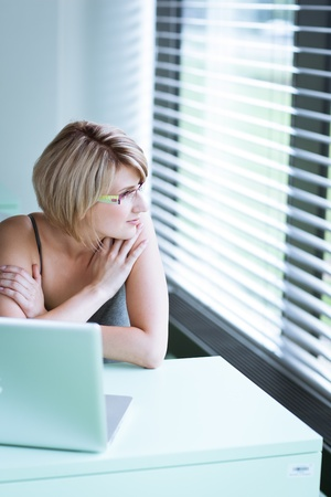 Portrait of a young woman pensively looking out of the window while sitting in front of her laptop Stock Photo - 10895319