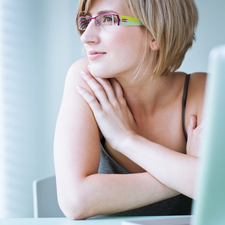 Portrait of a young woman pensively looking out of the window while sitting in front of her laptop Stock Photo - 10895232