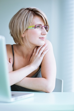 Portrait of a young woman pensively looking out of the window while sitting in front of her laptop Stock Photo - 10895378