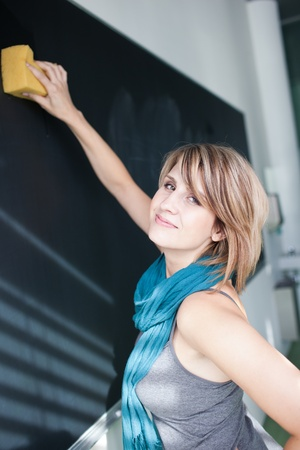 pretty college student erasing the chalkboard/blackboard during a math class (color toned image; shallow DOF) Stock Photo - 10895481