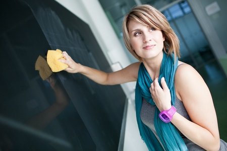 pretty college student erasing the chalkboard/blackboard during a math class (color toned image; shallow DOF) Stock Photo - 10895480
