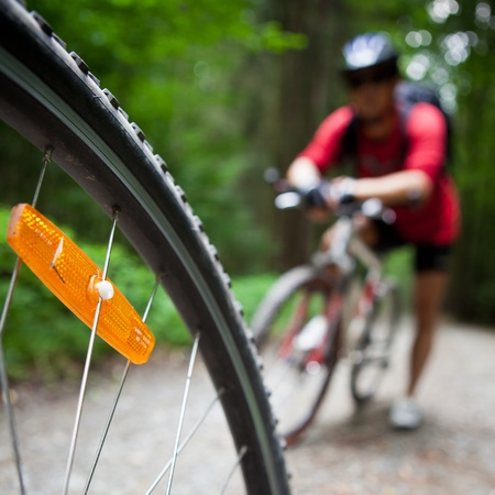 Mountain biking in a forest - bikers on a forest biking trail (shallow DOF, focus on the bike wheel in the foreground) photo