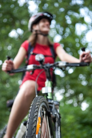 pretty young female biker outdoors on her mountain bike (shallow DOF; selective focus) photo
