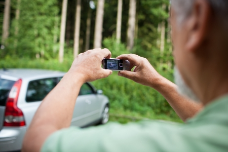 risk taking: Insurance company guy taking pics of a newly insured vehicle. Stock Photo