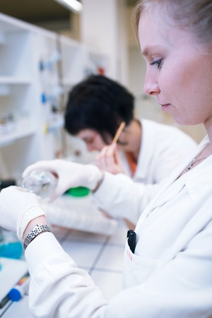 portrait of female researchers carrying out research in a chemistry lab (color toned image; shallow DOF) photo