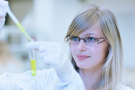 portrait of a female researcher carrying out research in a chemistry lab (color toned image; shallow DOF) photo