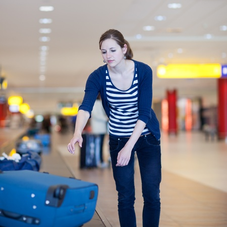 Baggage reclaim at the airport - pretty young woman taking her suitcase off the baggage carousel (color toned image) photo