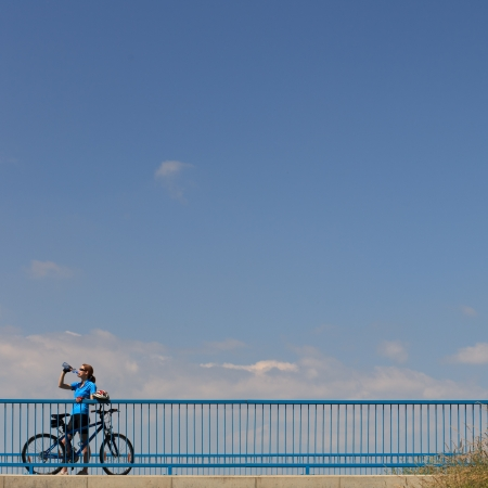 Background for poster or advertisment pertaining to cyclingsportoutdoor activities - female cyclist during a halt on a bridge against blue sky (color toned image) photo