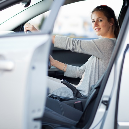Pretty young woman driving her new car photo