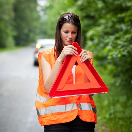 high visibility: Young female driver wearing a high visibility vestsafety vest, putting in place the warning triangle after her car has broken down