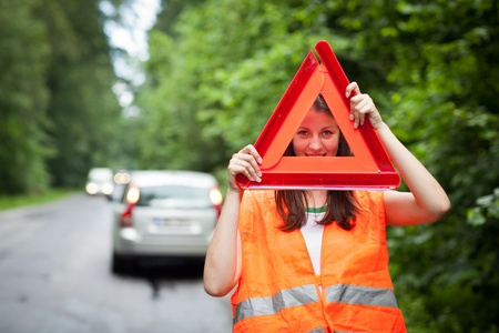 emergency vest: Young female driver wearing a high visibility vest, waiting for the roadside serviceassistance after her car has broken down