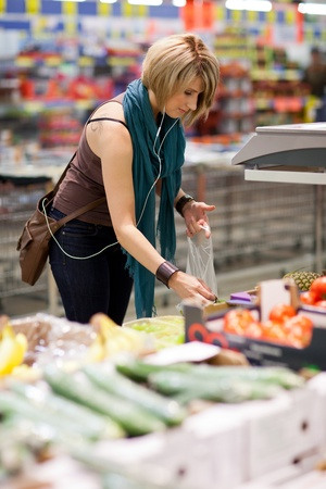 Beautiful young woman shopping for fruits and vegetables in produce department of a grocery store/supermarket photo