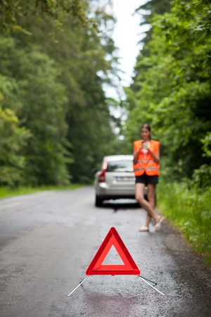 zichtbaarheid: Jonge vrouwelijke chauffeur het dragen van een hoge zichtbaarheid vest, het aanroepen van de kant van de weg dienst  bijstand nadat haar auto is afgebroken Stockfoto