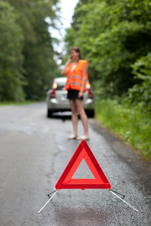 Young female driver wearing a high visibility vest, calling the roadside service/assistance after her car has broken down Stock Photo - 11073363