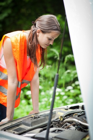 high visibility: Young female driver wearing a high visibility vest, checking the engine after her car has broken down Stock Photo