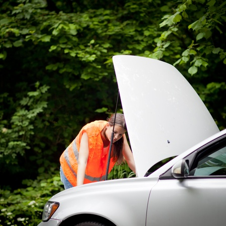 Young female driver wearing a high visibility vest, checking the engine after her car has broken down Stock Photo - 11073340