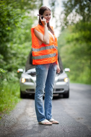 Young female driver wearing a high visibility vest, calling the roadside service/assistance after her car has broken down Stock Photo - 11073534
