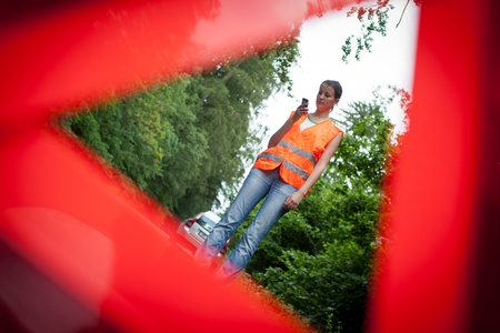 annoying: Young female driver wearing a high visibility vest, calling the roadside serviceassistance after her car has broken down Stock Photo