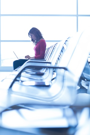 Young woman at the airport, working on a laptop and waiting for her flight Stock Photo - 11073343