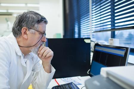 investigaci�n: investigador senior masculina llevar a cabo la investigaci�n cient�fica en un laboratorio (DOF, imagen en color entonado)