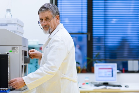 senior male researcher carrying out scientific research in a lab (shallow DOF; color toned image) photo
