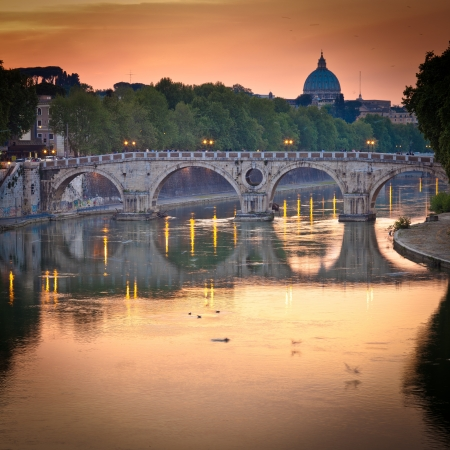 view of st. peters basilica and the river tiber at sunset - rome, italy photo