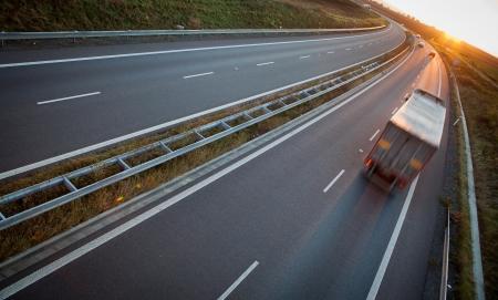 lorry: traffico autostradale - movimento ha offuscato camion su una strada  autostrada  superstrada al crepuscolo (immagine a colori tonica)