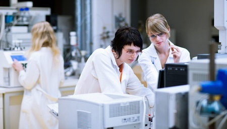 chromatograph: two female researcherschemistry students doing research in a chemistry lab (color toned image; shallow DOF)