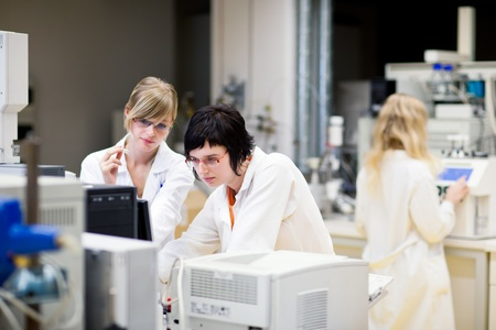 scientific equipment: two female researcherschemistry students doing research in a chemistry lab (color toned image; shallow DOF)