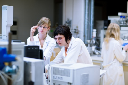two female researcherschemistry students doing research in a chemistry lab (color toned image; shallow DOF) photo