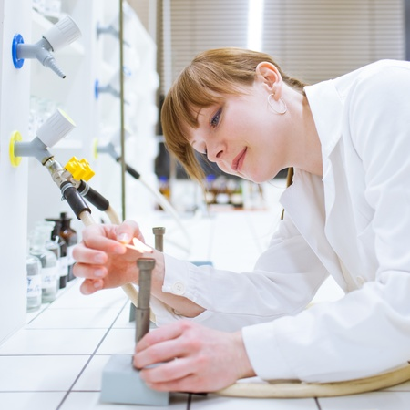 pretty female researcher/chemistry student lighting up a burner in a lab (color toned image) Stock Photo - 11237996