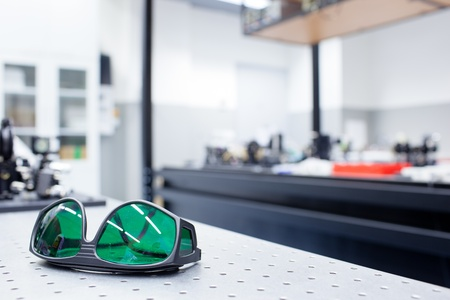 quantum optics lab - shallow DOF; selective focus on the protective goggles in the foreground (color toned image) photo