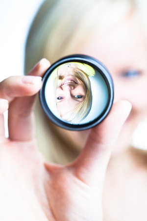 Optics concept: pretty young woman showing the principle of imaging through a lens (focus on the image through lens) photo