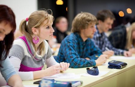pretty, female college student sitting in a classroom full of students during class (shallow DOF; color toned image) photo