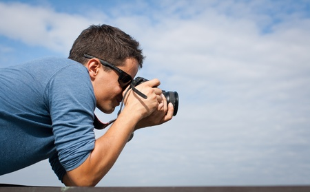 Handsome young professional photographer taking photos against blue sky photo