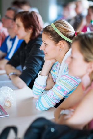 adult classroom: young, pretty female college student sitting in a classroom full of students during class (shallow DOF; color toned image) Stock Photo