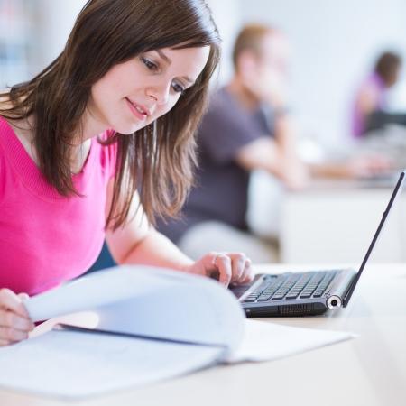 in de bibliotheek - mooie vrouwelijke student met laptop en boeken die werkzaam zijn in een middelbare school bibliotheek (kleur getinte afbeelding)