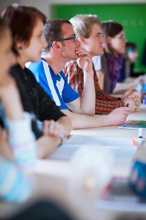 tanulás: fiatal, jóképű egyetemista ül egy osztályteremben teljes tanulók az órán Stock fotó