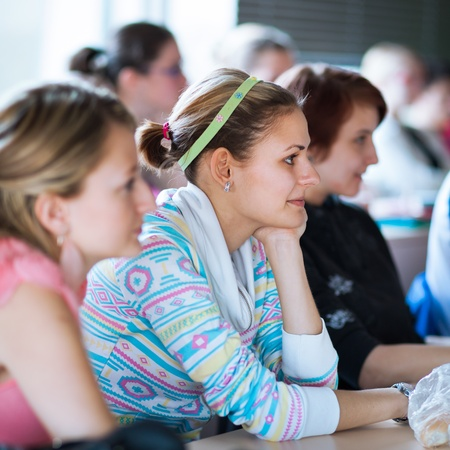 young, pretty female college student sitting in a classroom full of students during class (shallow DOF; color toned image) photo