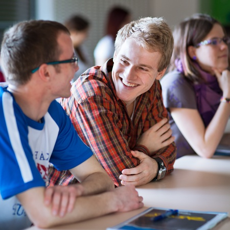 young, handsome college student sitting in a classroom full of students during class Stock Photo - 11303371